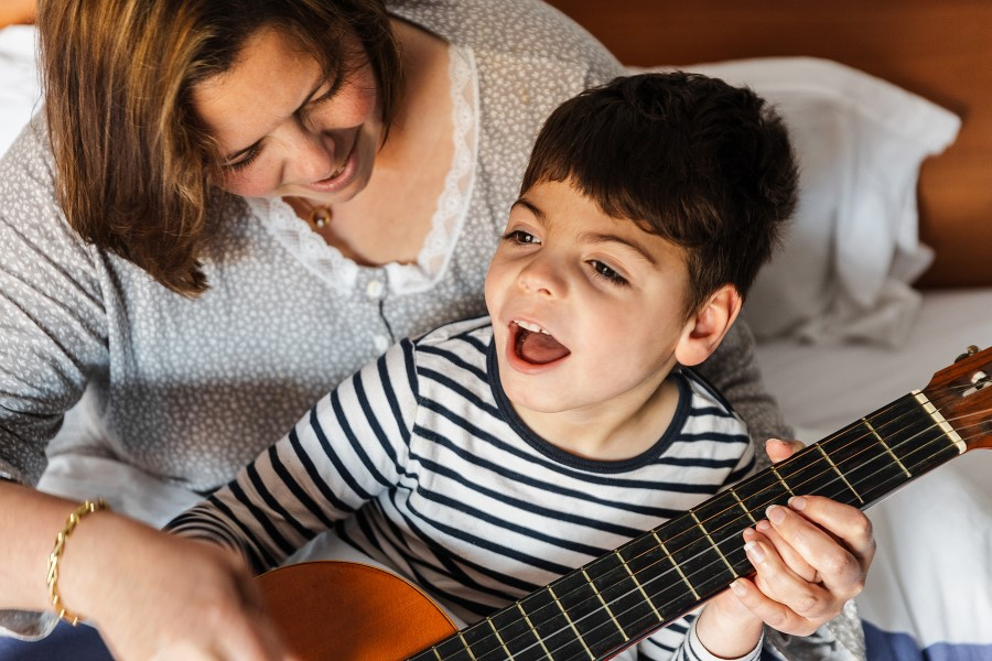 mother helps son learn guitar