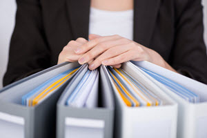 woman rests hands on three ring binders