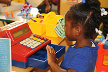 Child playing with toy cash register