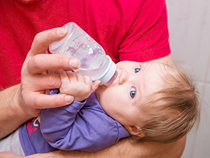 father feeding baby with bottle