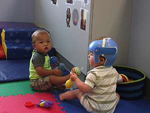two infants, one with a helmet, playing with a ball and shaker