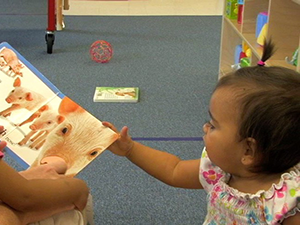 baby reaching for a book.