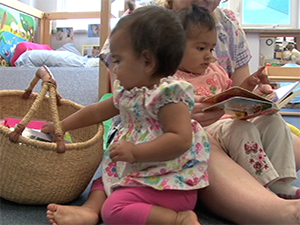Child care provider reading to toddlers.