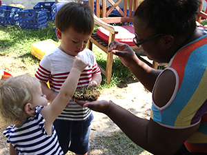 2 toddlers explore a piece of turf with a childcare giver outside