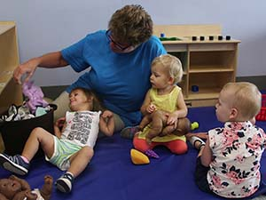 Child care provider playing with children.