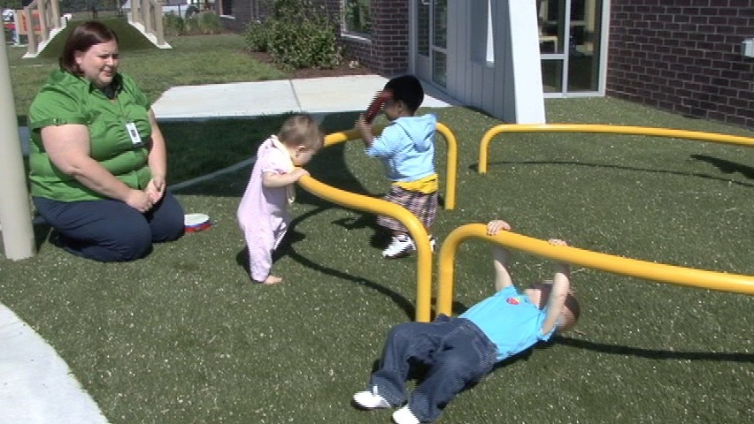 Teacher and toddlers play outdoors.