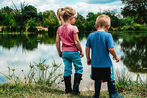 children in boots look at a lake
