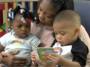 child care provider reading to two children